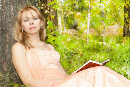 Attractive woman sleeping with book against a tree Stock Photo