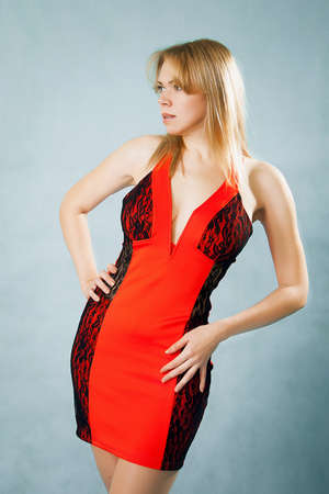 beautiful woman in sexy red dress standing on blue background