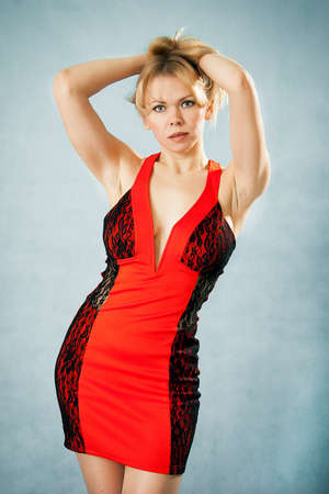 Attractive woman in red evening dress with hands on her hair Stock Photo