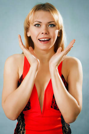 Surprised pretty woman in red dress on blue background photo