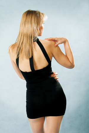 beautiful woman in sexy black dress standing with her back against blue background