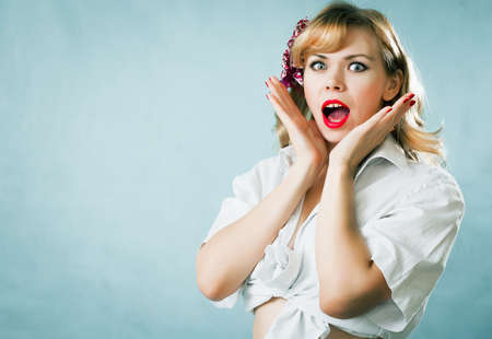 Pin-up young blonde woman on blue background Stock Photo