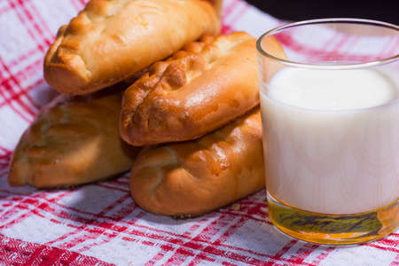 red tablecloth: Hot tasty pies on red tablecloth with cup of milk Stock Photo