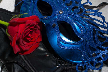 Composition of erotic black corset, red rose and blue mask Banque d'images