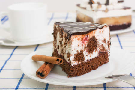 tort: slice of chocolate sponge cake with a cherry and air souffle covered with chocolate icing on a white plate with cinnamon sticks Stock Photo