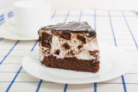 tort: slice of chocolate sponge cake with a cherry and air souffle covered with chocolate icing on a white plate