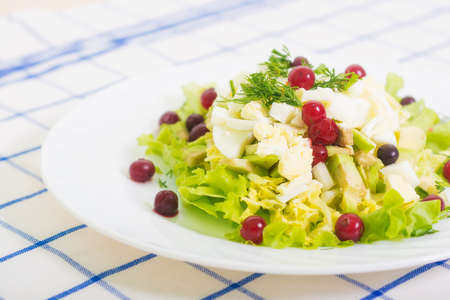 cowberry: dietary salad from avocado, eggs, and cowberry on blue tablecloth