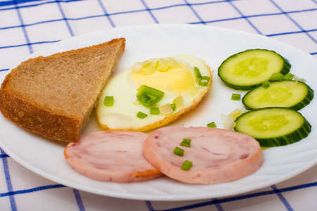 english cucumber: fried eggs with bacon on white plate served with a slice of black bread and sliced cucumber. Sprinkle with pepper and green onions.