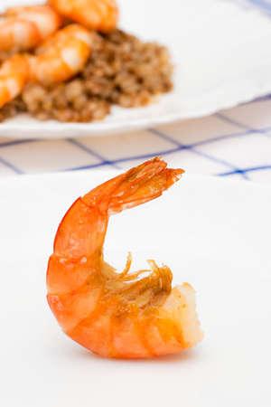 camaron: camarones fritos en aceite colocado sobre un plato blanco. En el fondo es un plato de camarones y el trigo sarraceno