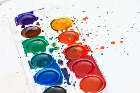 paintbox: The palette of childrens watercolor paint on white sheets of paper. Background image. Splashes of colorful and divorces.