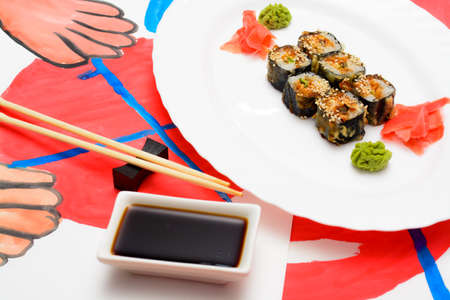 Fud art. Japanese sushi on a white plate on the tablecloth are made watercolor paint abstract image of human hands holding chopsticks