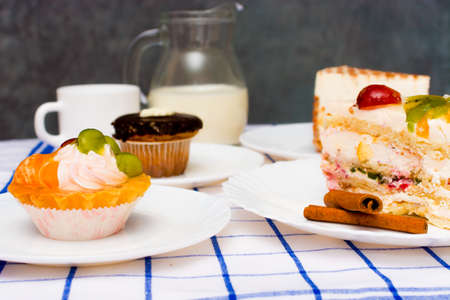 cake basket with fruit and cream. in the background there are dishes with various other dessert, a cup of tea (coffee), a jug of milk Stock Photo