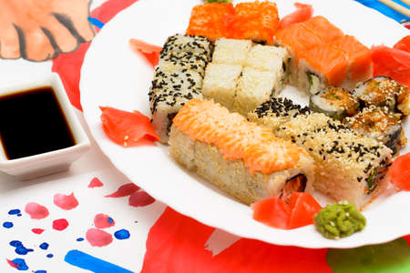 Water Fud art. Japanese sushi on a white plate on the tablecloth are made of watercolor paint with an abstract image of the flag of Japan, chopsticks for sushi picture sushi. Stock Photo