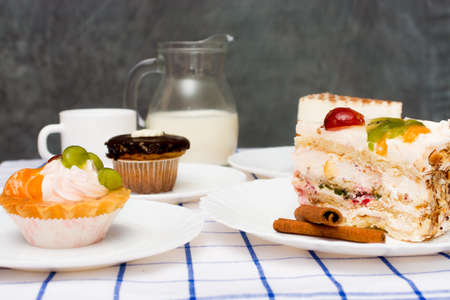 piece of cake on a white plate. in the background there are dishes with various other dessert, a cup of tea (coffee), a jug of milk and two cinnamon sticks Stock Photo
