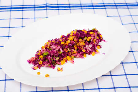 salad of red cabbage, onion, yellow corn and apple on white plate