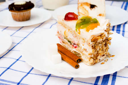 piece of fruit cake on white plate as table decorations cinnamon sticks and other desserts