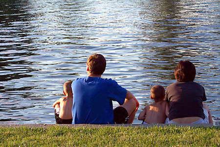 Family outdoors sitting by river.