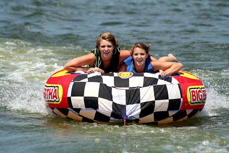 Teenage girls tubing on lake. Reklamní fotografie