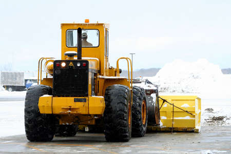 snow plow: Snow plow removing pile of snow at airport