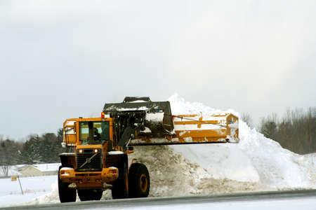 snow plow: Snow plow adding to pile of snow at airport Stock Photo