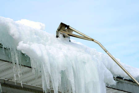 rake: snow rake removing snow and ice from roof