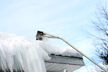 rake: Snow rake removing snow and ice from roof Stock Photo