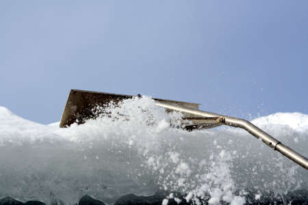 Snow rake removing ice and snow from roof Reklamní fotografie