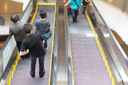 People in motion in escalators at the modern shopping mall photo