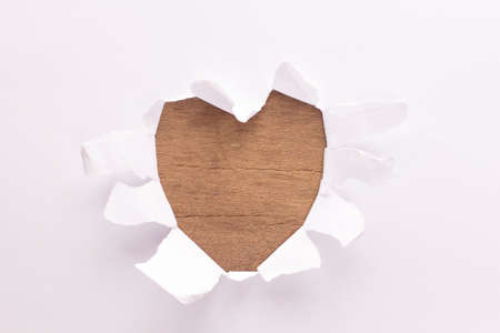 Sheet of paper with a Heart shape hole against bright wood background isolated on white photo