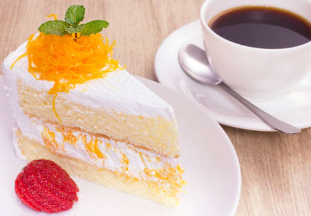 cake on the white plate with a cup of coffee