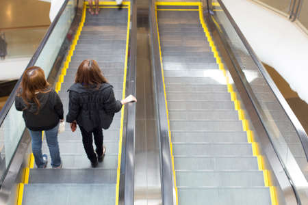 view of a staircase in a shop: People in motion in escalators at the modern shopping mall
