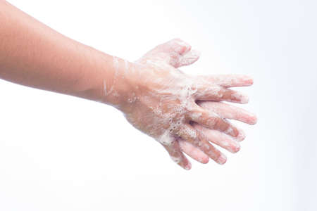 A man washes he hands with soap. Isolated on white photo