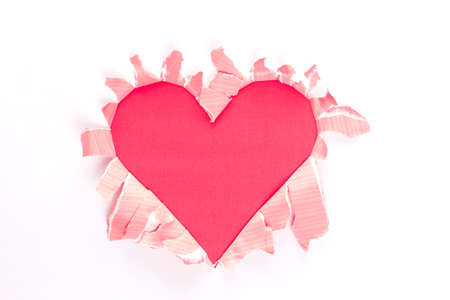 Sheet of paper with a Heart shape hole against bright pink background isolated on white photo