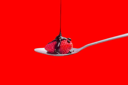Chocolate syrup being poured onto a strawberry in a spoon photo