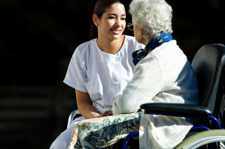 young girl medical personel helping an old woman photo