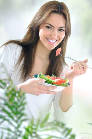 dieta sana: joven y bella mujer comiendo ensalada Foto de archivo
