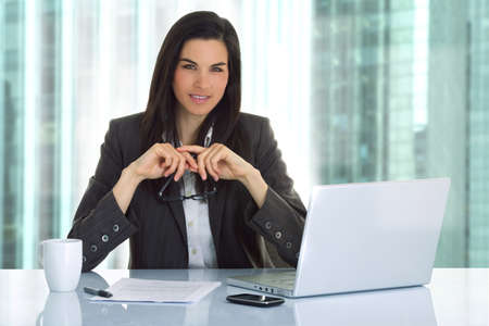 Business woman in an office with laptop Stock Photo