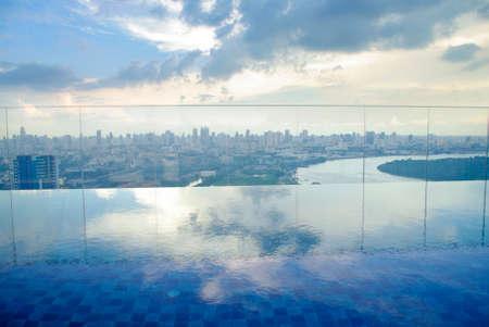 높은 condominuim 건물에 인피니티 풀. 강과 도시의 스카이 라인의 아름다운 전망 스톡 콘텐츠