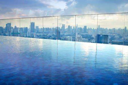 infinity pool on high condominuim building. beautiful view of river and city skyline