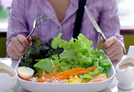 girl with knife and fork eating salad photo