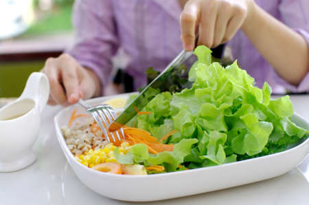 girl eating salad with knife and fork photo