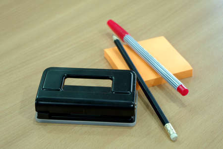 paper punch: Paper Punch, pencil, post note and red pen on wood table Stock Photo