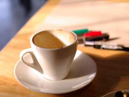 Empty coffee cup on the wood table with pens and paper on the background photo