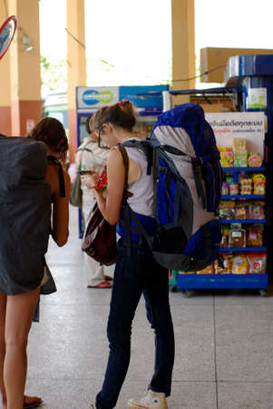 backpacker traveler in thailand, using smartphone at bus terminal