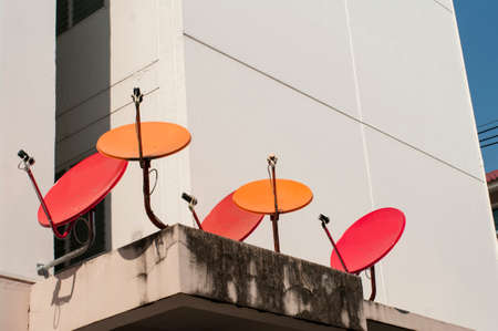 red and orange satellite dishes on top of roof photo