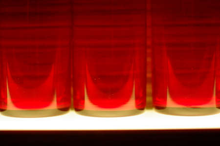 red light illuminated glass bottle abstract background photo