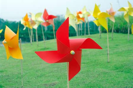 colourful windmill field in grass field photo