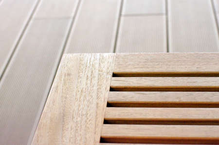 wood seat and deck next to the pool photo