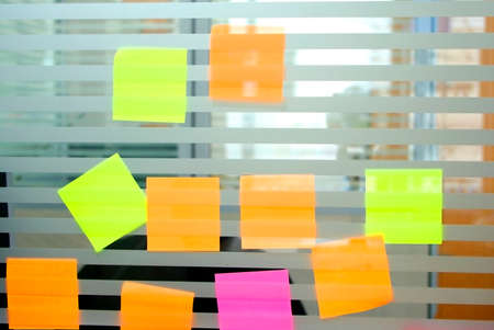 glass partition: colourful blank paper note on glass partition Stock Photo
