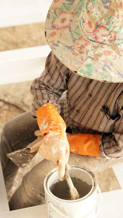 homeownership: worker working on painting detail with stain orange glove Stock Photo